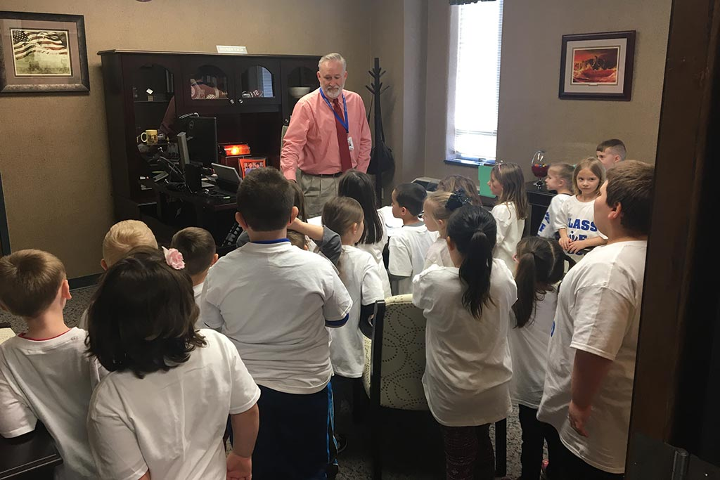 man looking over group of kids in an office