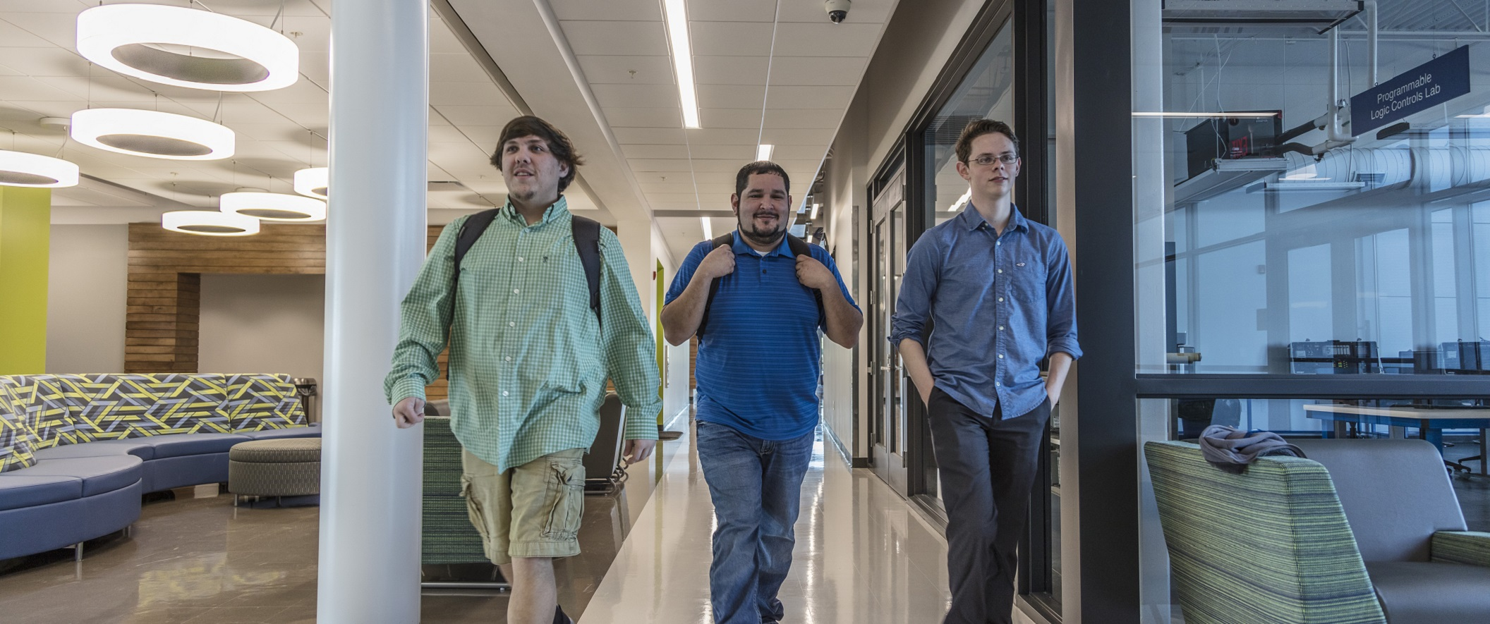 three male students walking down a hallway
