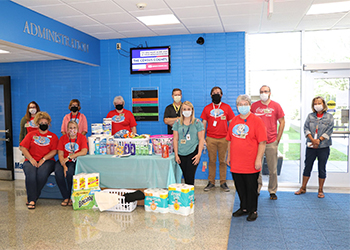 Administrative Professionals group on the Maysville Campus standing next to the donations they collected for the Women's Crisis Center in Maysville.