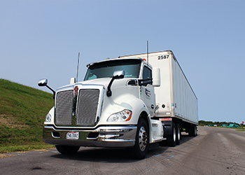 A large, white semi truck parked and photographed from the front against a clear blue sky.