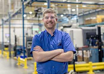 MCTC grad Landon Garrison wearing safety glasses at his workplace, facing the camera and smiling.