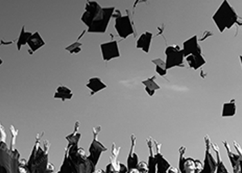 Black and white photo of graduation caps being tossed into the air.