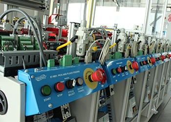Row of blue machines with multi-color control panels in the robotic lab on the Rowan Campus of MCTC.