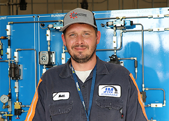 Student Matthew Miller standing in front of a blue manufacturing training machine.