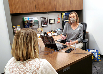 Tonya Arnett, SSS employee, meeting with a student in her office space while practicing social distancing and both wearing face masks.