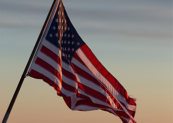 United States flag waving against sunset.
