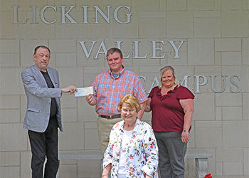 Student Nicholas Allen Morris pictured with his family in front of the Licking Valley Campus building receiving his scholarship.