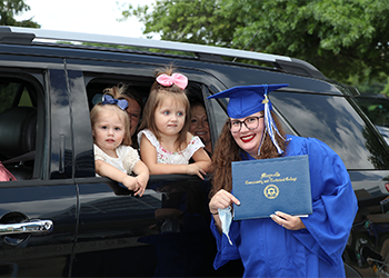 Female graduate standing by her car displaying her certificate, with her children looking out the car window.