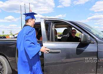 Student in graduation cap and gown getting back into black truck.