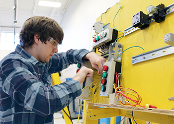 Student working on an advanced manufacturing trainer machine.