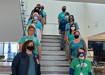 Group of faculty, staff and students wearing teal shirts.