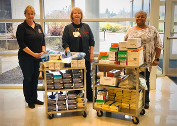 MCTC employees standing with two carts of supplies they are donating to local health care.