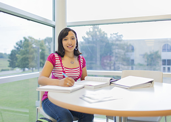 MCTC graduate Rosa Delgado sitting at a desk on campus as a student.