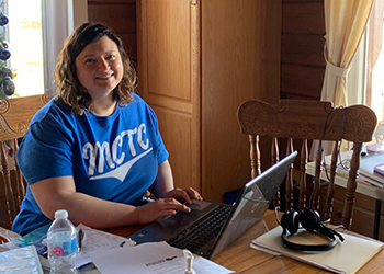 Michelle Thoroughman smiling, working at home from her kitchen table.